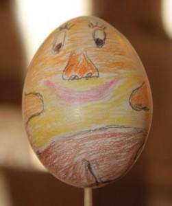 Ei Nummer 5 zeigt ein aus Kreide gemaltes Oster-Gesicht in vielen bunten Farben.