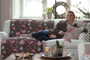 Zu sehen ist ein Quilt, welches auf beiden Seiten verschiedene Muster hat, sowie ein helleres Kissen mit dem markanten Blumenmuster.